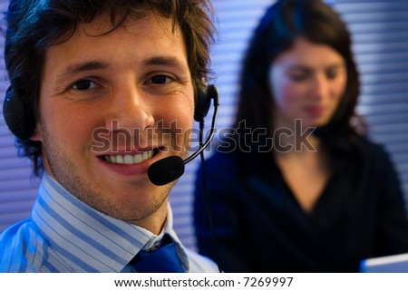 Male and female customer service representative working in office, smiling. - stock photo