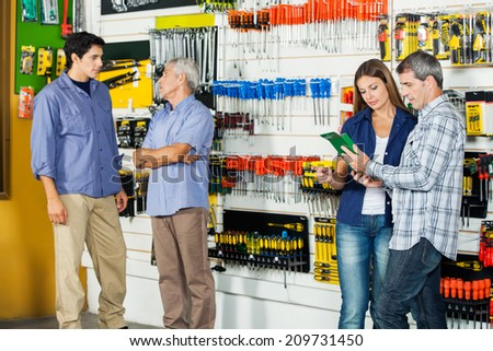 Male and female customers in hardware store - stock photo