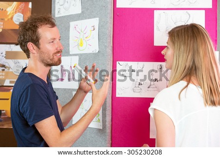 Male and female 3D designers discussing over charts in printing studio - stock photo