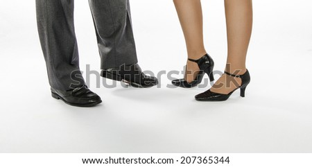Male and female dancers feet in crocodile leather shoes standing on white background - stock photo