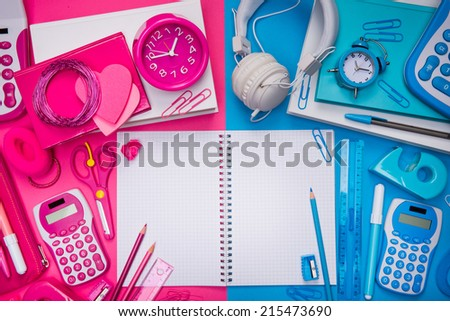 Male and female desktop with stationery and open notebook at center. - stock photo