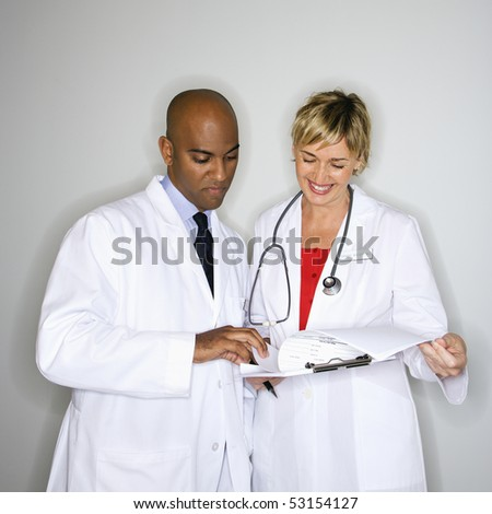 Male and female doctors reading paperwork. - stock photo