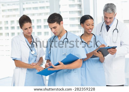 Male and female doctors working on reports in the hospital - stock photo
