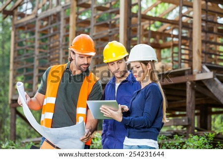 Male and female engineers using digital tablet while reviewing blueprint at construction site - stock photo