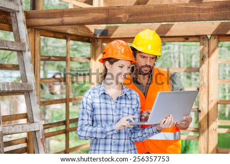 Male and female engineers working on laptop together at construction site