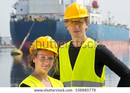 Male and female entrepreneurial engineers posing happily in front of a large industrial vessel - stock photo