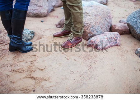 male and female feet on the rocky beach - stock photo
