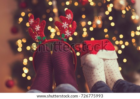 Male and female feet wearing warm winter socks with Santa's hat and antlers with Christmas tree and Christmas lights in background. Selective focus on the antlers