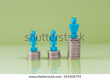 Male and female figurines standing on top of columns of coins. Wage gap concept illustration. - stock photo