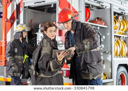 Male and female firefighters using tablet computer against truck at fire station
