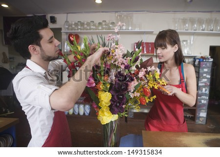 Male and female florists working together in flower shop - stock photo