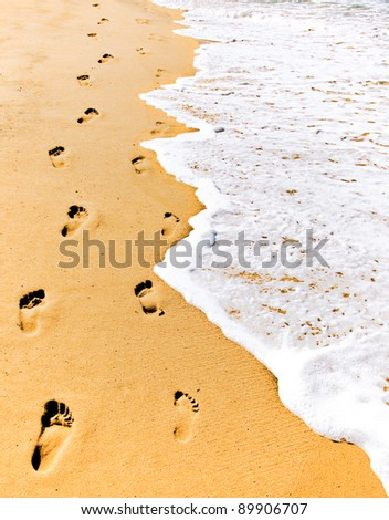 Male and female footsteps imprinted side by side in the sand. - stock photo