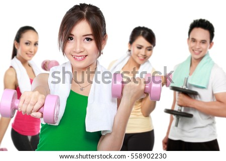 male and female friends doing exercise together at the gym using dumbbell
