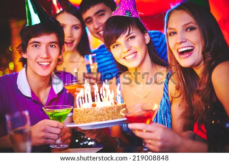 Male and female friends holding cake with burning candles and drinks on birthday party - stock photo