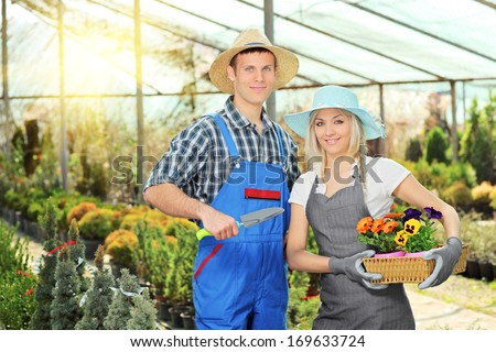 Male and female gardeners with basket full of flowers and small shovel posing in hothouse - stock photo