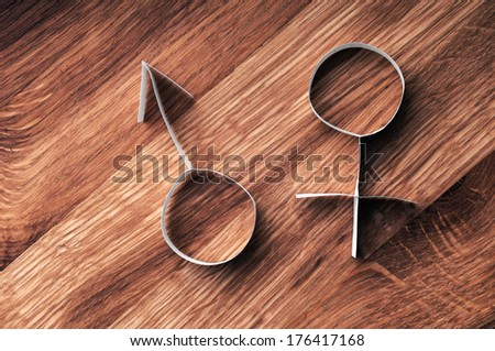 Male and female gender symbols, mars and venus on wooden background. - stock photo