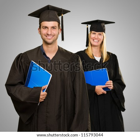 Male And Female Graduate Students Holding Book - stock photo