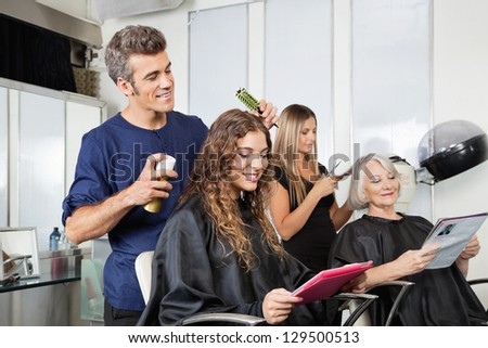 Male and female hairdressers setting up client's hair in beauty salon