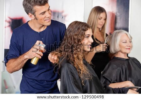 Male and female hairdressers setting up client's hair in salon