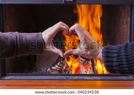 male and female hand forming heart at fireplace - stock photo