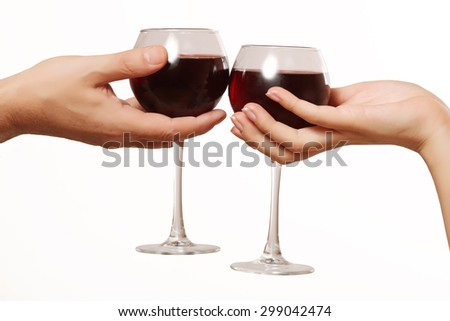 male and female hand holding glasses of red wine, romantic dinner - stock photo