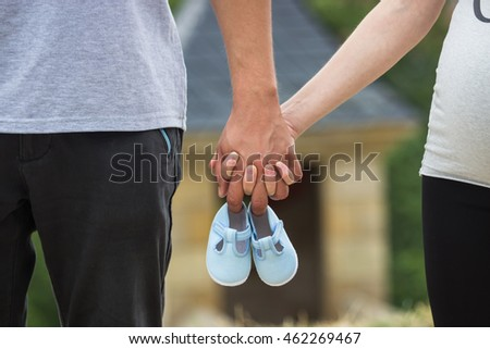 Male and female hands holding a baby shoes