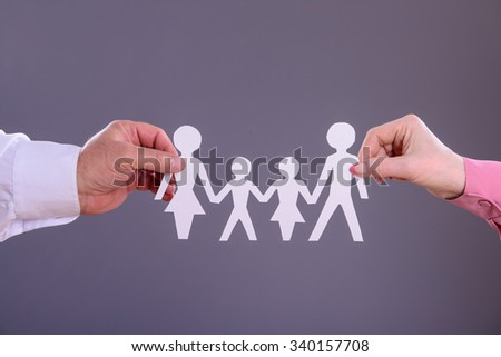 Male and female hands holding a paper family - stock photo