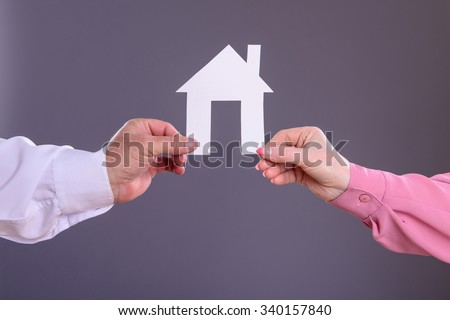 Male and female hands holding a paper house - stock photo