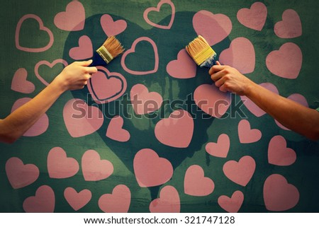 Male and female hands holding brushes and painting concrete wall with hearts - stock photo