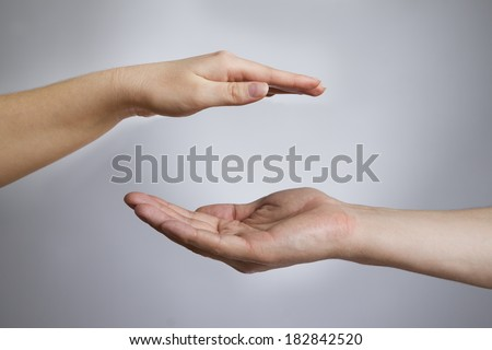 Male and female hands on a gray background. Empty outstretched palm. Copy space - stock photo