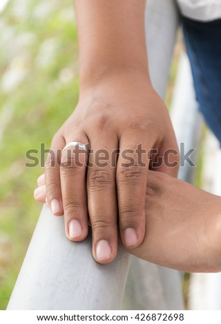 Male and female hands touching with wedding ring - stock photo