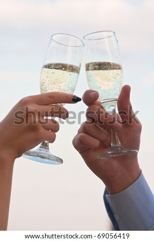 Male and female hands with champagne in wineglasses