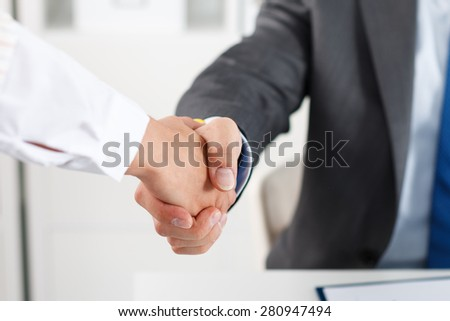 Male and female handshake in office. Businessman in suit shaking woman's hand. Serious business and partnership concept. Partners made deal and sealed it with handclasp. Formal greeting gesture - stock photo