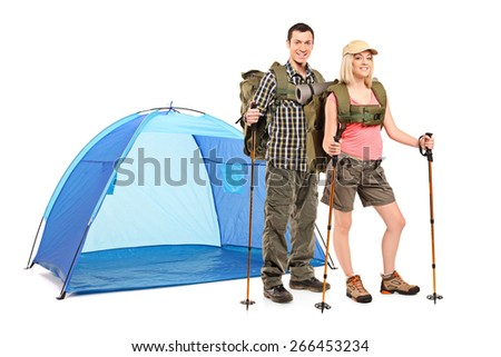 Male and female hiker standing next to a blue tent and carrying hiking equipment isolated on white background