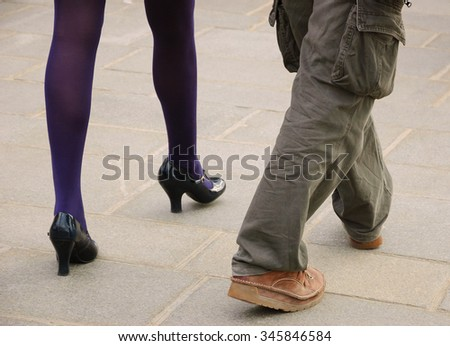 Male and female legs. Closeup. Couple on the bridge over Seine river in Paris. Gender and lifestyle differences concept.