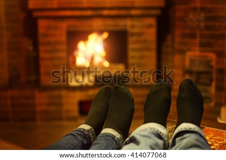 male and female legs near the fireplace. Family concept - stock photo