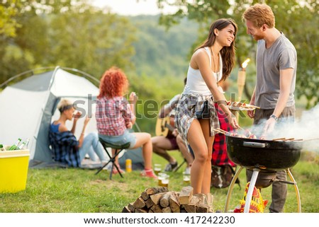 Male and female lovingly look each other while baked barbecue in green nature