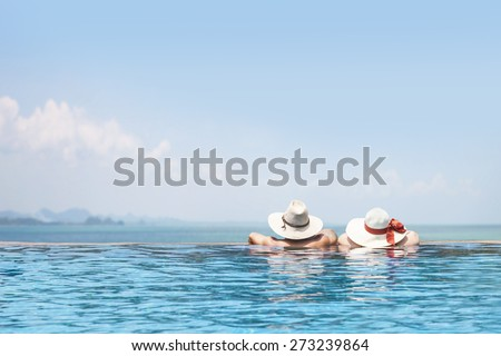 male and female models in the swimming pool wearing hats facing to the sea, beautiful summer vacation poster background, happy tour, enjoy travel, tourism, fun trip - stock photo
