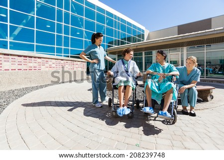 Male and female patients on wheelchair looking at each other by nurses outside hospital building - stock photo