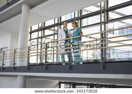 Male and female physicians talking on the balcony - stock photo