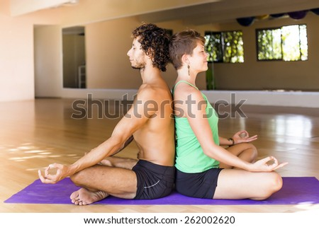 Male and female practicing meditation together - stock photo