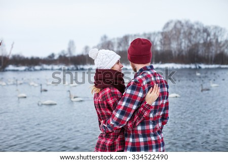 male and female shirts and caps embrace on a background of Swan Lake - stock photo