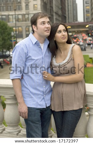 Male and female standing outside staring to the side - stock photo
