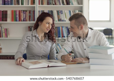 Male and female student in library studying for exam. Group of two students doing research. Bookshelves in background.