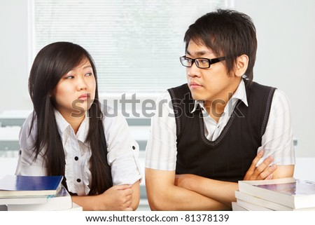 Male and female student looking each other full of hatred - stock photo