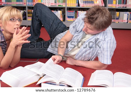 male and female students reviewing material from the books in the library - stock photo