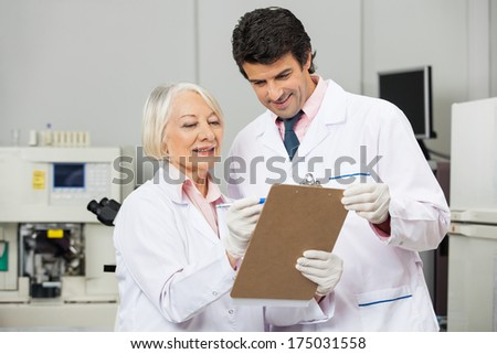 Male and female technicians writing on a clipboard in medical laboratory - stock photo