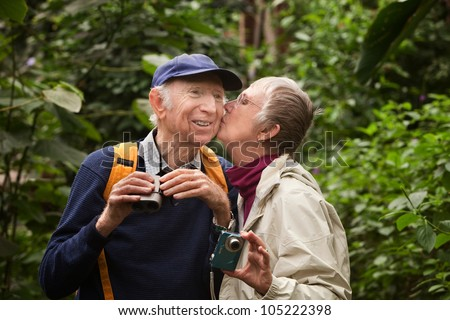 Male and female tourists kissing in the forest - stock photo