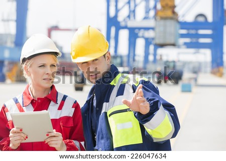 Male and female workers discussing in shipping yard - stock photo