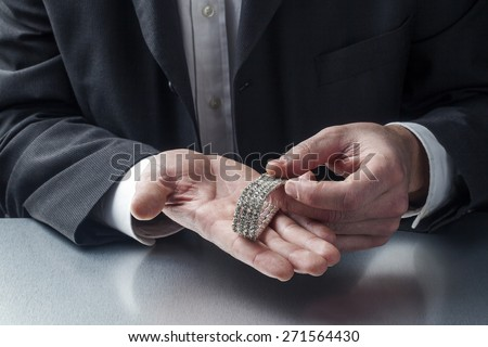 male appraiser with bracelet in hands